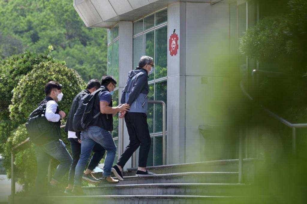 Cheung Kim Hung, CEO and Executive Director of Next Digital Ltd, is escorted by police into the Apple Daily newspaper offices in Hong Kong