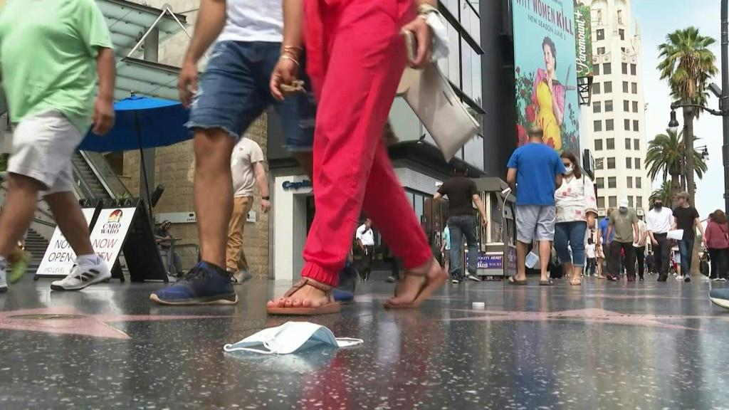"""People walk down Hollywood Boulevard in Los Angeles as California -- the first US state to enact a stay-at-home order just under 15 months ago -- celebrates its """"reopening day"""" by lifting almost all pandemic-related social distancing and capacity limits."""