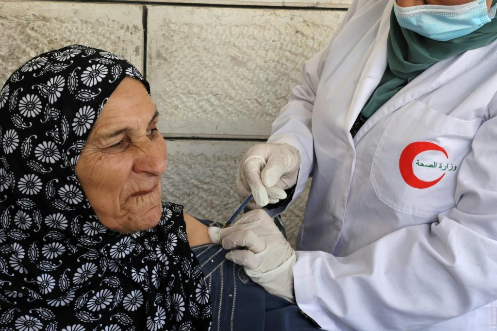 A mobile Covid inoculation unit vaccinates an elderly Palestinian in the village of Dura in the Israeli-occupied West Bank