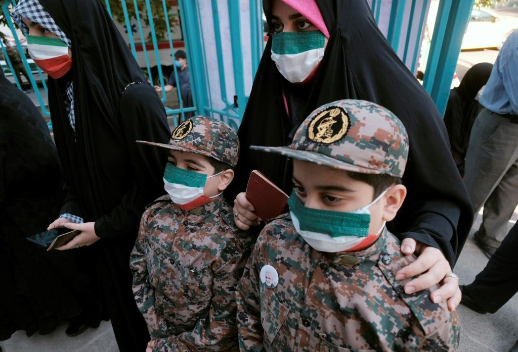 An Iranian woman queues to vote in Tehran, accompanied by her sons wearing Revolutionary Guard uniforms