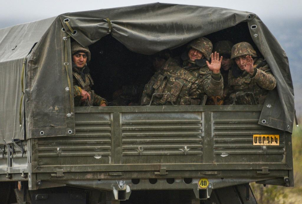 Armenian soldiers wave goodbye as they leave the town of Agdam last November before the territory wasreturned to Azerbaijan as stipulated in the Moscow-brokered peace deal