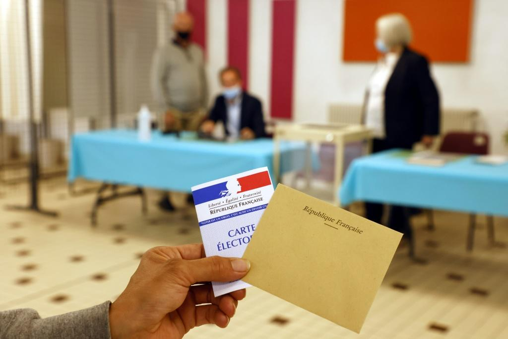 A voter shows an electoral card and a ballot envelop at a polling station in Cucq, northern France