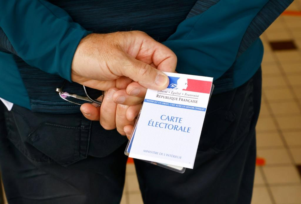 A voter waits with his electoral card to cast his ballot at a polling station in Cucq, Northern France, for the first round of the French regional elections