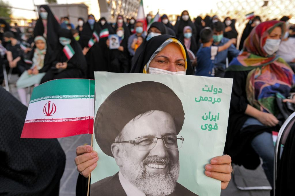 """A woman holds a poster of Iran's newly-elected president Ebrahim Raisi, with text in Persian reading """"government of the people, strong Iran"""", as supporters celebrate his victory in Imam Hussein square in the capital Tehran on June 19, 2021"""