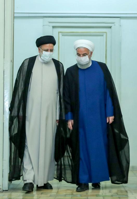 Raisi (L) is pictured meeting with outgoing President Hassan Rouhani in this picture provided by the presidential office on June 19, 2021