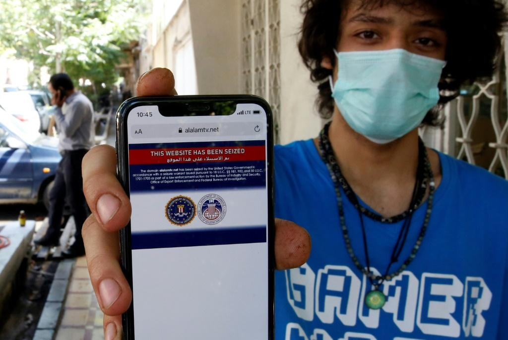 An Iranian youth shows on his mobile phone a statement declaring the website of Iran's Arabic-language channel Al-Alam has been seized by the US government