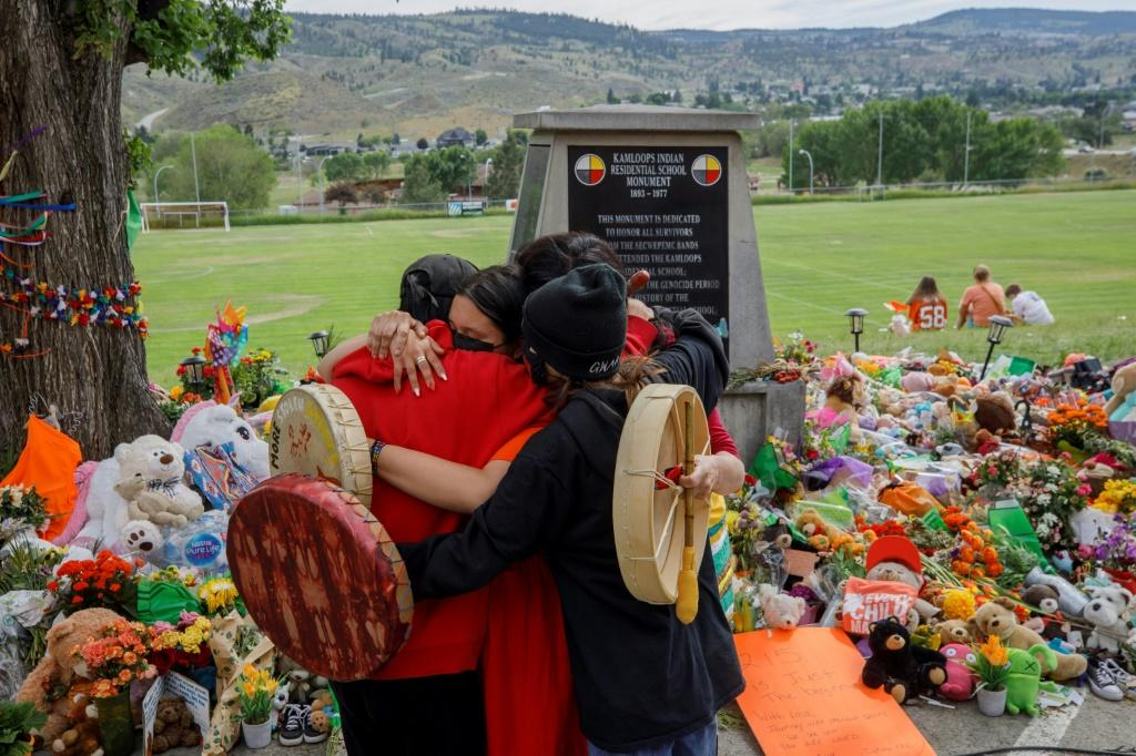 People from Mosakahiken Cree Nation hug in front of a makeshift memorial at the former Kamloops Indian Residential School to honour the 215 children whose remains have been discovered buried near the facility, in Kamloops, British Columbia, Canada, on Jun