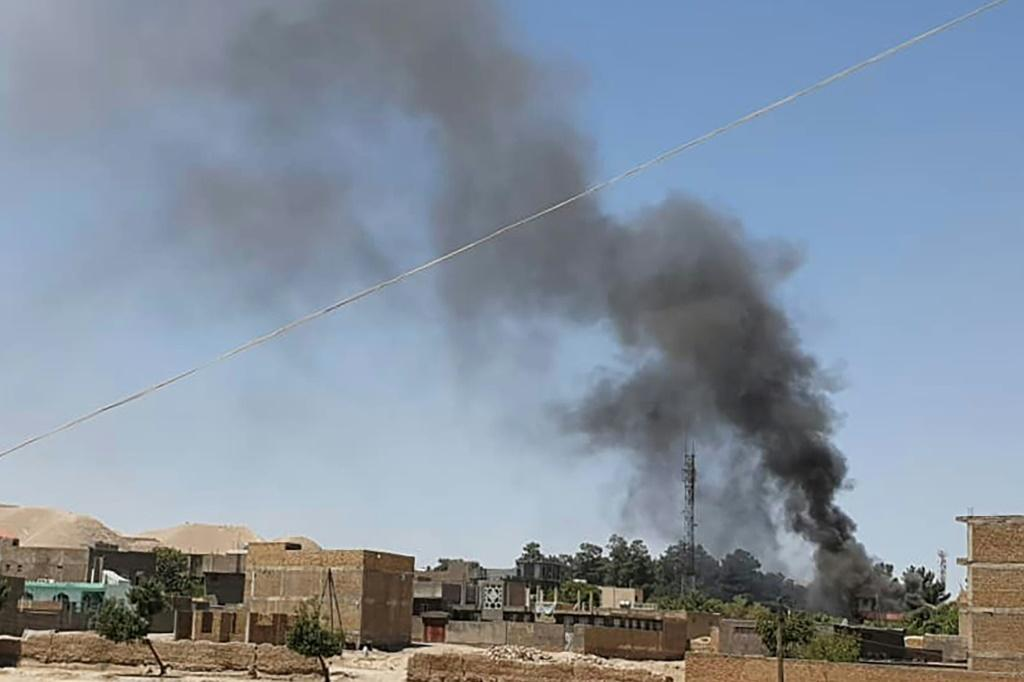 A smoke plume rises from houses as clashes rage between Afghan security forces and Taliban fighters in the western city of Qala-i-Naw in Afghanistan