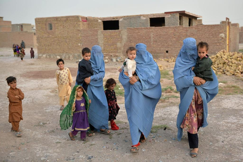 Members of an internally displaced Afghan family who left their home during the ongoing conflict between Taliban and Afghan security forces arrive from Qala-i-Naw, in Enjil district of Herat, on July 8, 2021