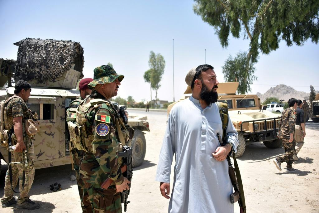 Afghan security personnel stand guard along the road amid ongoing fight between Afghan security forces and Taliban fighters in Kandahar