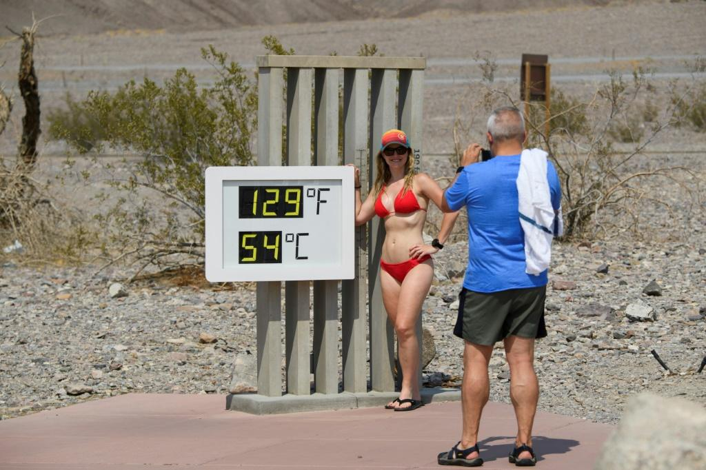 Tourists pose next to a thermometer in California's Death Valley in June. Sweltering conditions have hit much of the Pacific seaboard and as far inland as the western edge of the Rocky Mountains over the weekend