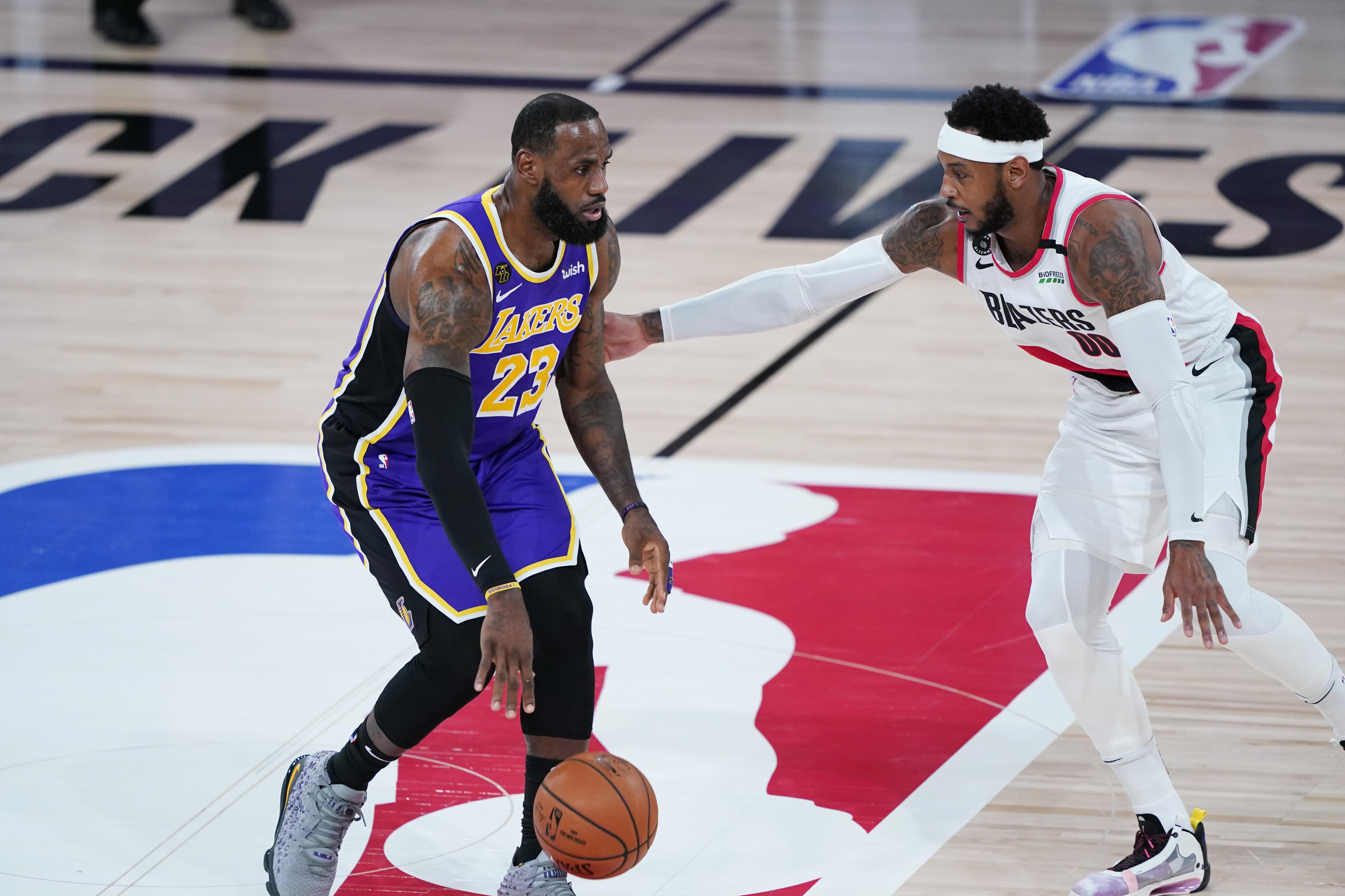 LeBron James #23 of the Los Angeles Lakers drives against Carmelo Anthony #00 of the Portland Trail Blazers
