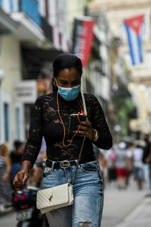 A woman uses her phone in a street of Havana, on July 14, 2021