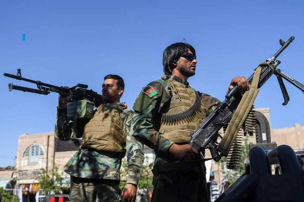 Afghan security personnel stand guard outside the blue mosque during the Eid al-Adha prayers in Herat