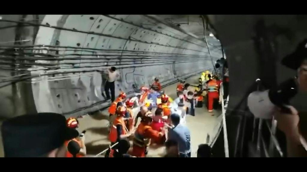 Firefighters rescue trapped passengers from a flooded subway station in the central Chinese city of Zhengzhou, where deadly torrential rains have wreaked havoc.