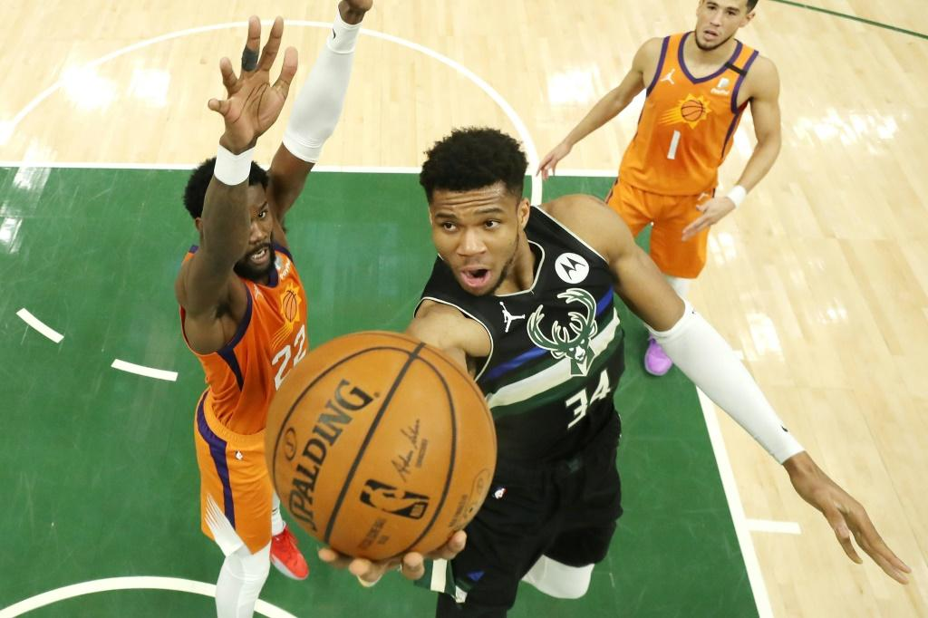 Milwaukee Bucks star forward Giannis Antetokounmpo goes up for a shot past Phoenix's Deandre Ayton in Tuesday's sixth game of the NBA Finals, in which the Greek star scored 50 points to power the Bucks over the Suns to win their first title since 1971
