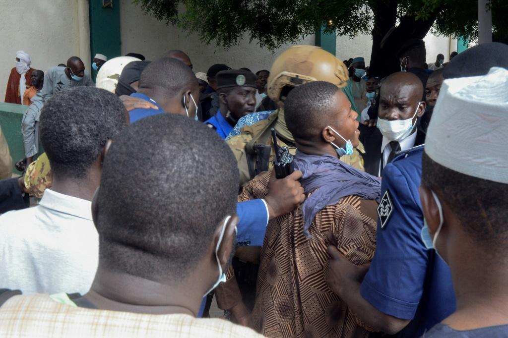Security personnel escort an alleged attacker from the mosque
