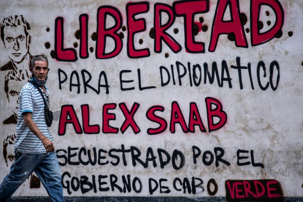 """A man walks past a graffiti reading """"Freedom for diplomat Alex Saab, kidnapped by the government of Cape Verde"""" in Caracas, on February 23, 2021. Colombian businessman Saab, who is allegedly close to Venezuelan President Nicolas Maduro has been sanctioned"""