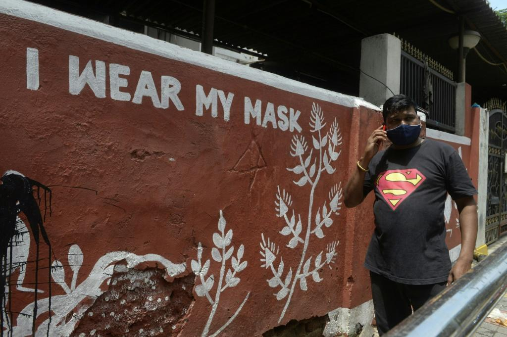 A man walks past a mural with a message spreading awareness about Covid-19 in Hyderabad