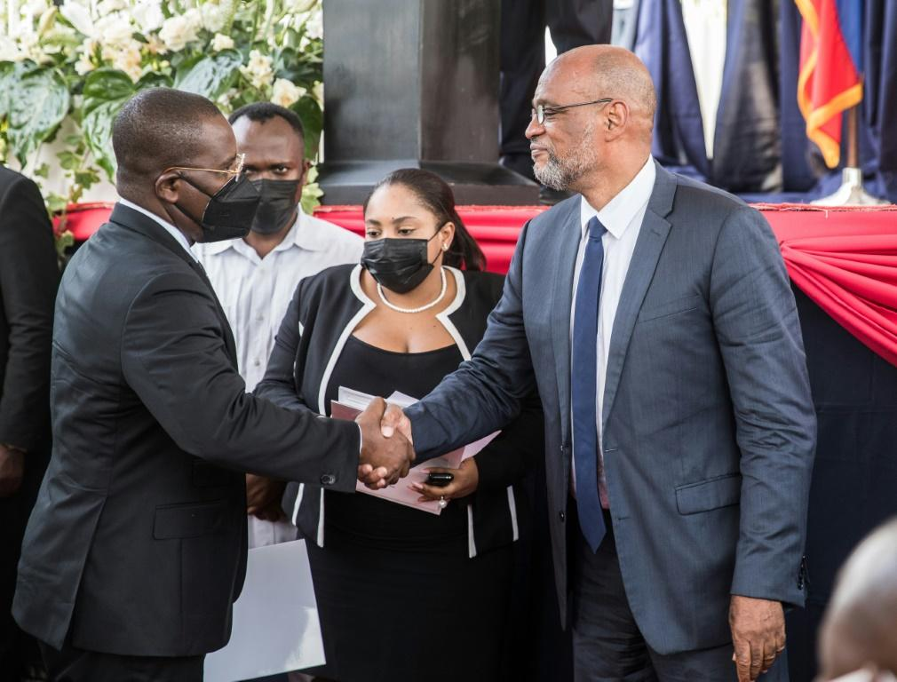 Haiti's new prime minister Ariel Henry (R) shakes hands with his predecessor Claude Joseph, who led the country in the wake of Jovenel Moise's assassination