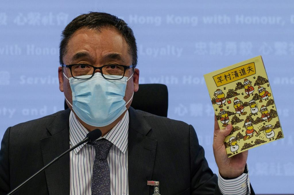 Hong Kong Senior Superintendent Steve Li, from the city's new national security police unit, holds up one of the allegedly seditious children's books