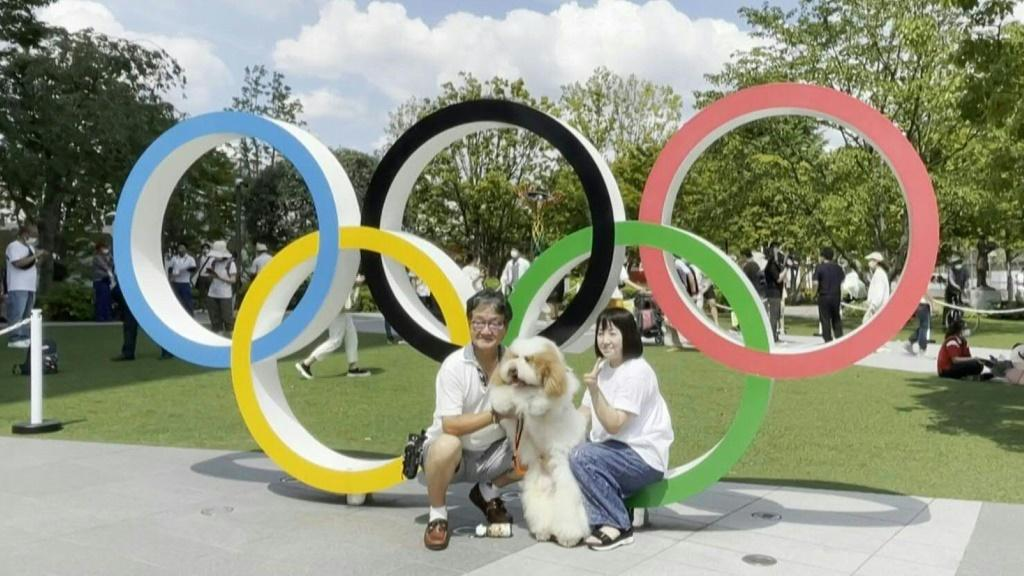 Hours ahead of the opening ceremony of the Tokyo 2020 Olympics, people take photos outside the Olympic Stadium.