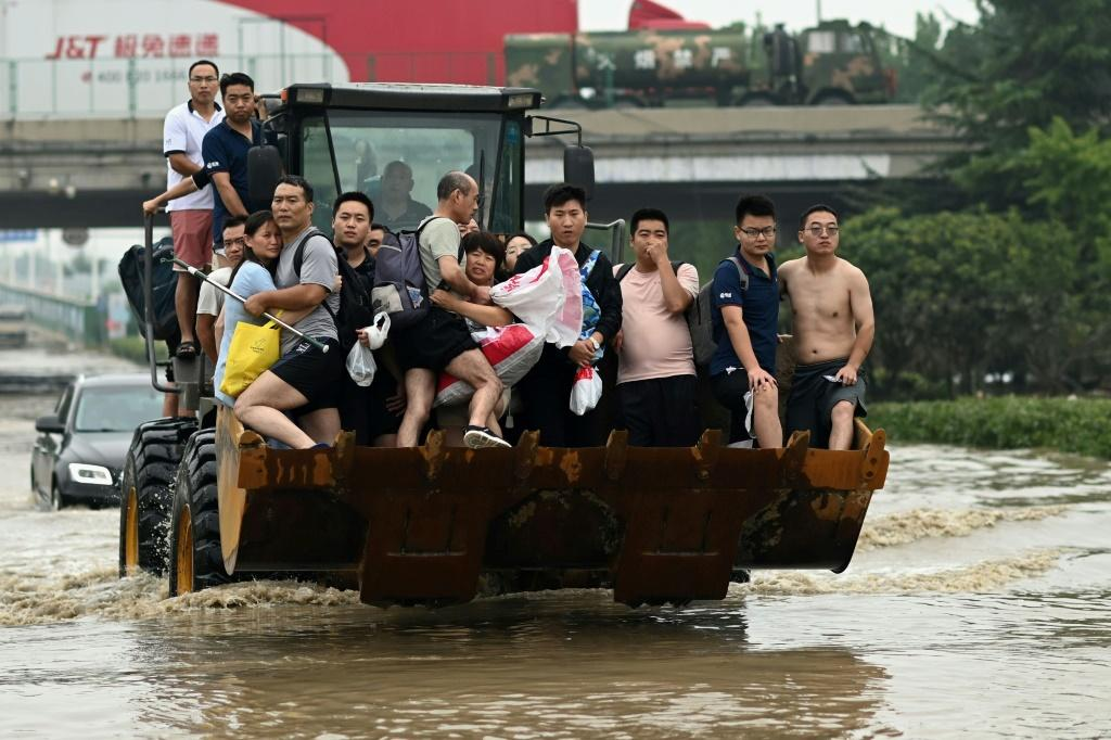 People are carried across a flooded street in the worst-hit city of Zhengzhou, which received a year's worth of rain in just three days