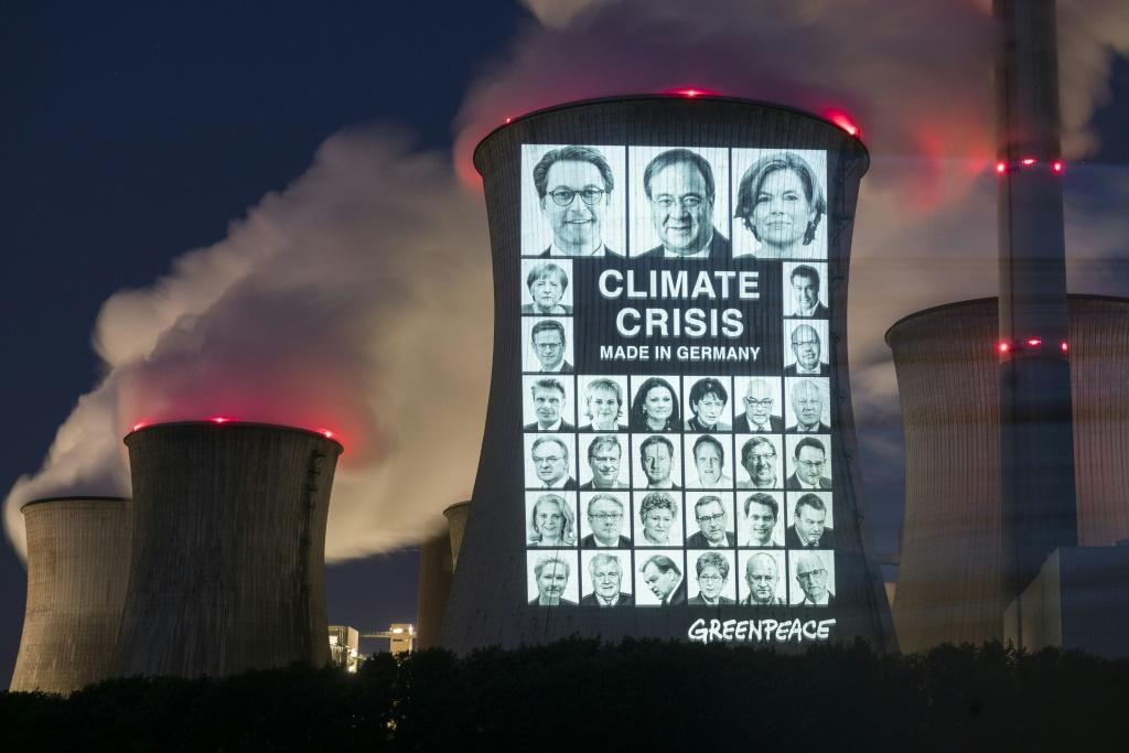 """Portraits of 31 politicians are projected with the slogan """"Climate crisis, made in Germany"""" onto a cooling tower of the brown coal power station in in Grevenbroich"""