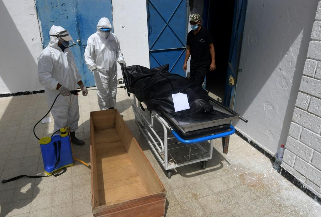 Tunisian municipal employees disinfect the body of a COVID-19 victim at the Ibn al-Jazzar hospital in the city of Kairouan earlier this month