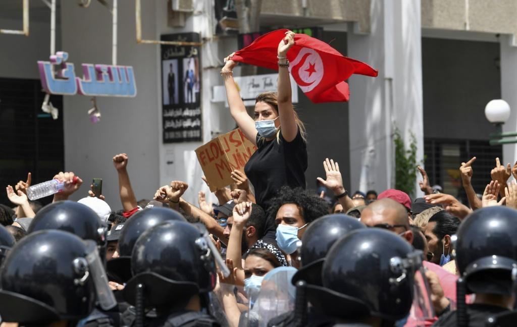 A Tunisian protester waves the national flag at an anti-government rally in front of parliament in Tunis on Sunday