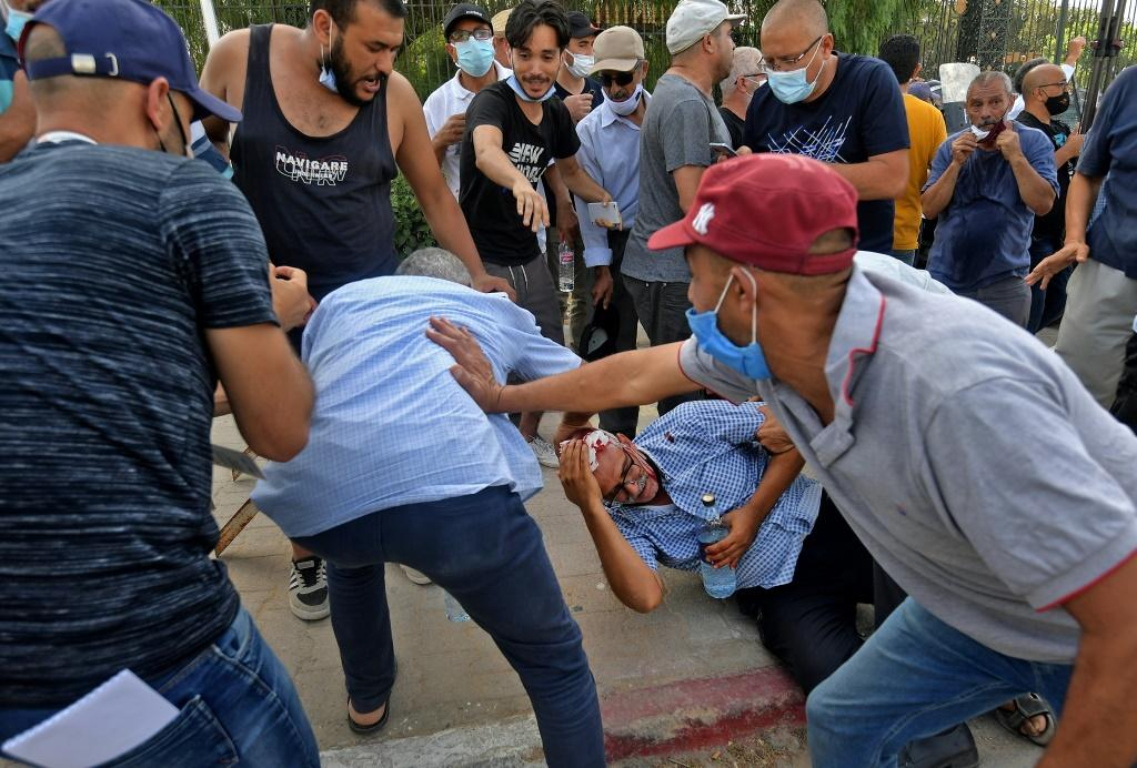 A supporter of the country's Islamist Ennahdha party (on the ground C) is injured by a stone thrown at him during a protest outside the parliament building in the capital Tunis on Monday