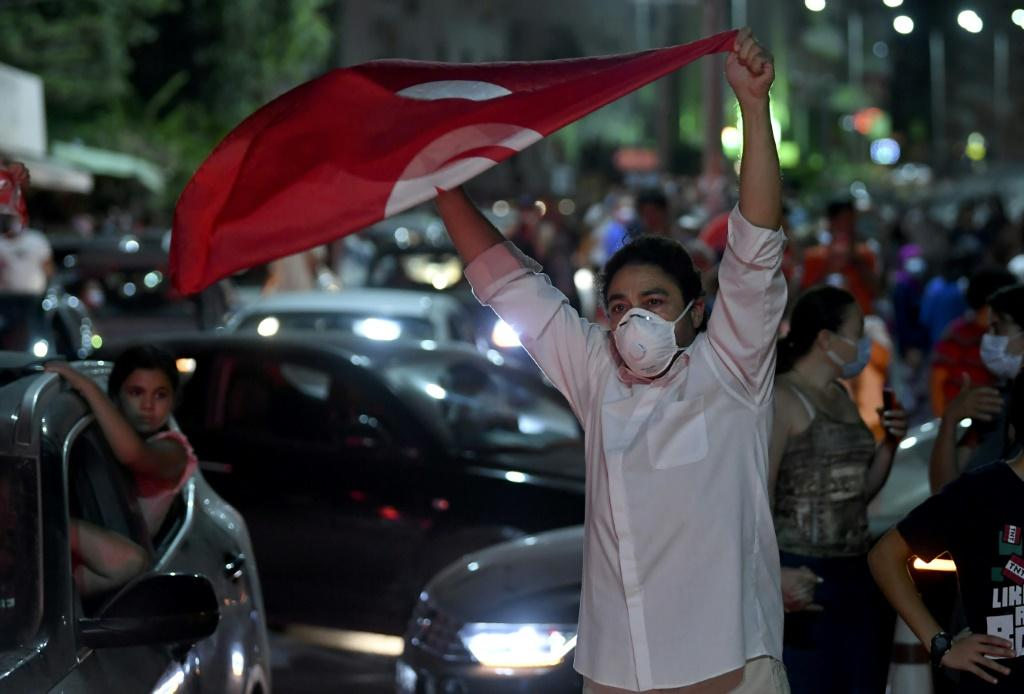 People celebrate in the streets of Tunis after Tunisian President Kais Saied announced the suspension of parliament and the dismissal of the prime minister