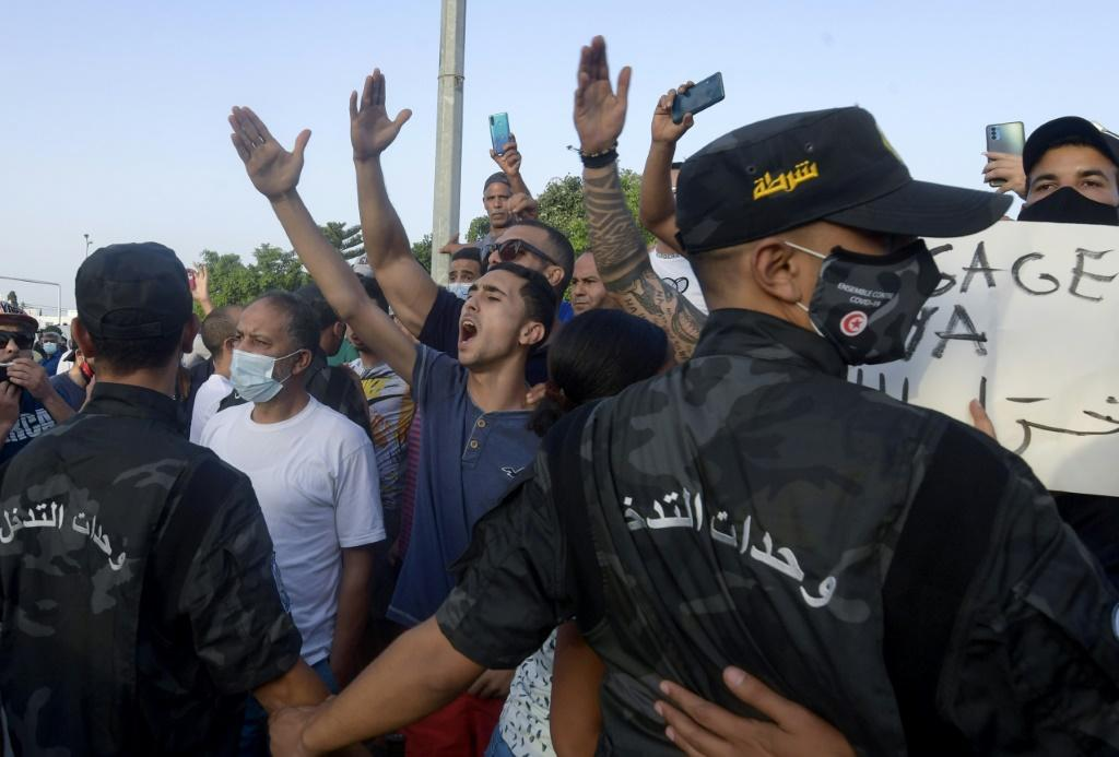 Tunisian security officers hold back supporters of President Kais Saied as they chant slogans against the country's largest political party near parliament on Monday