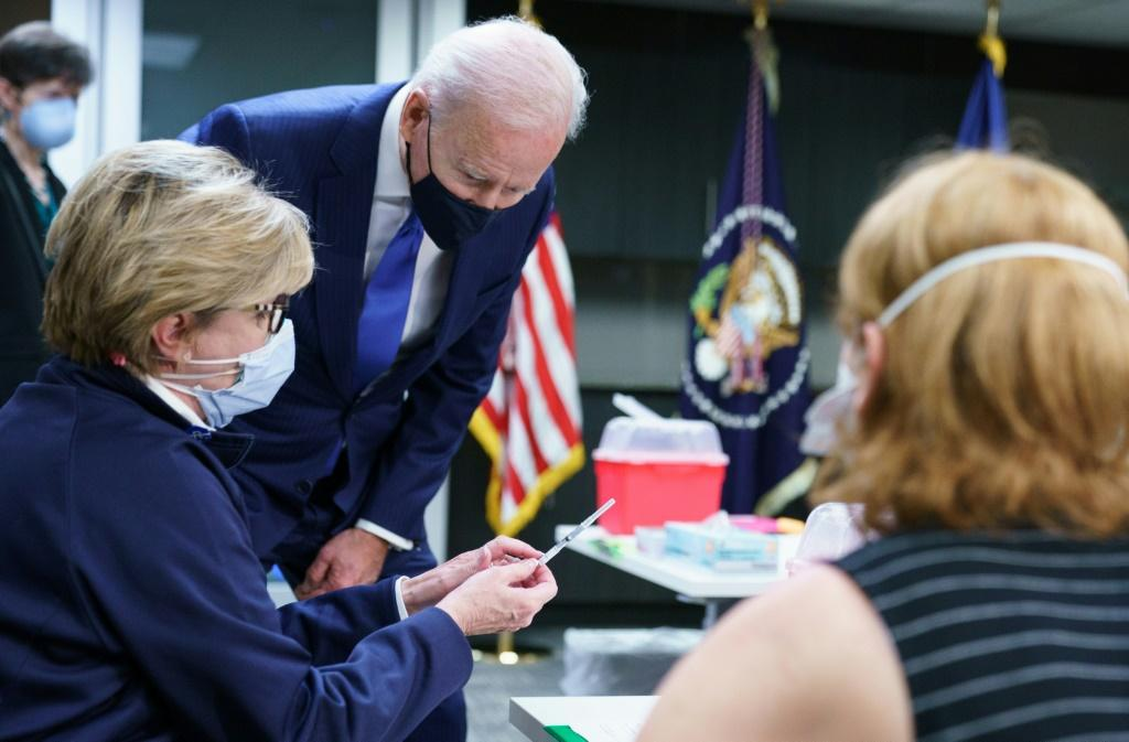 US President Joe Biden looks at a dose of vaccine before its administered at a Covid-19 vaccination site at the Washington DC Veterans Affairs Medical Center in Washington