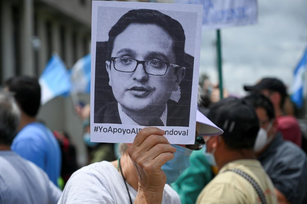 A demonstrator holds a portrait of dismissed special prosecutor Juan Francisco Sandoval during a protest outside the Public Ministry's headquarters in Guatemala City on July 24, 2021