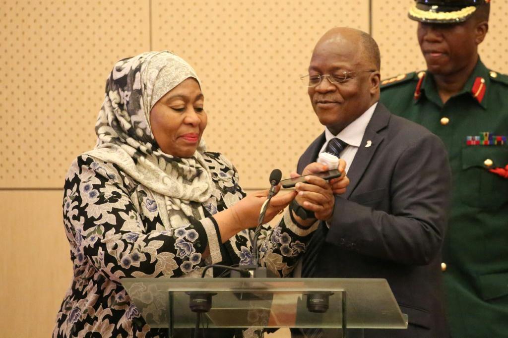 Former president John Magufuli and his deputy, Samia Suluhu Hassan. They are pictured speaking on a mobile phone to Kenyan leader Uhuru Kenyatta in July 2019