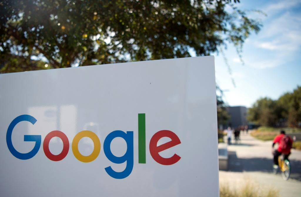A man rides a bike passed a Google sign and logo at the Googleplex in Menlo Park, California on November 4, 2016