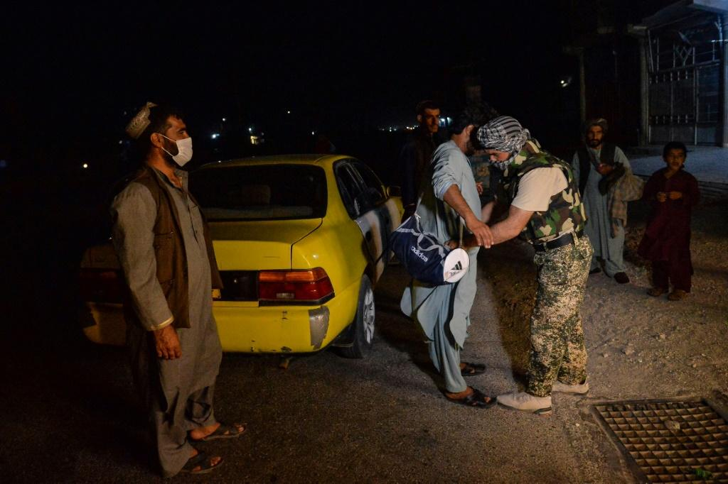 Afghan security force personnel searching a commuter at a checkpoint in Herat, western Afghanistan