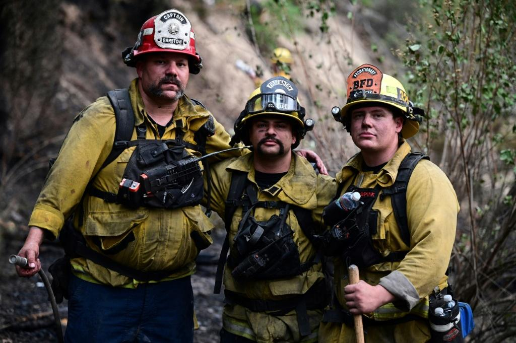 Firefighters -- such as these pictured taking a breather as they put out hot spots from the Dixie Fire, in Twain, California -- are increasingly reaching out to support groups to deal with the stress of ever-longer fire seasons
