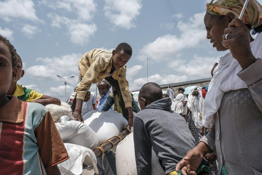 A young person arranges a sack of wheat on a cart during food distribution organized by the Amhara government near the village of Baker, 50 kilometers southeast of Humera, in the Tigray region of Ethiopia, on July 11, 2021.