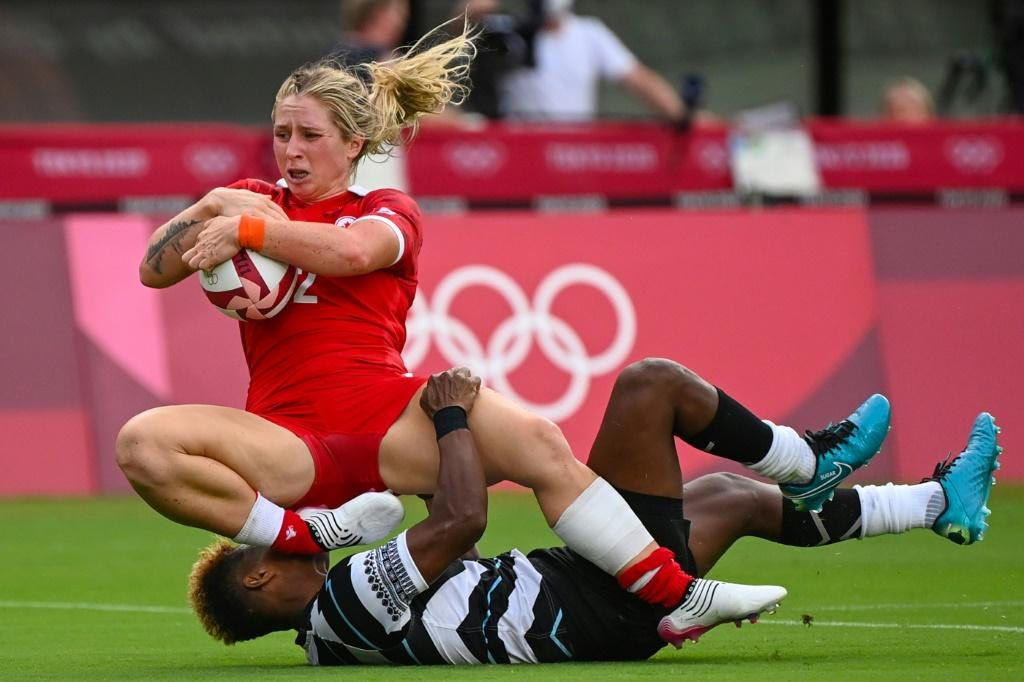 Canada's Kayla Moleschi (left) evades a tackle by Fiji's Roela Radiniyavuni to score a try in the women's pool B rugby sevens match between Canada and Fiji during the Tokyo 2020 Olympic Games.