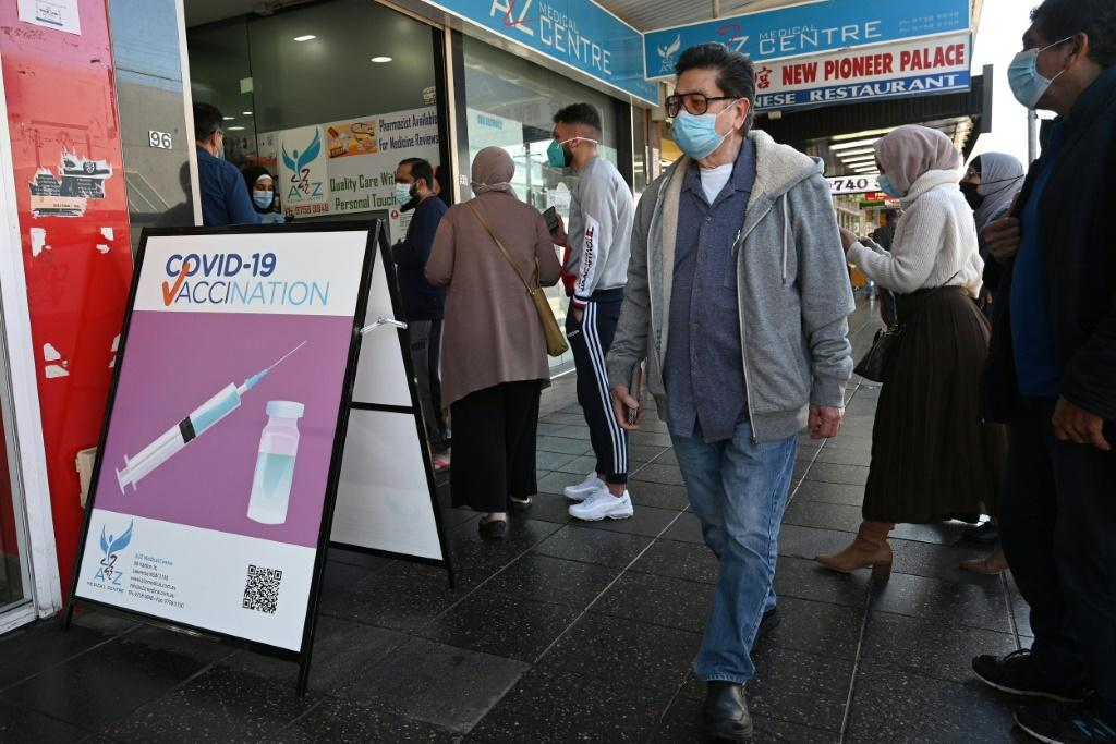 Sydney residents queue outside a pharmacy for a Covid-19 vaccination. Prime Minister Scott Morrison said Australia will reopen its borders and end lockdowns when 80% of the population is fully vaccinated