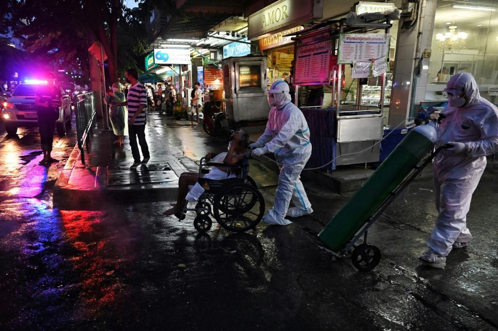 An elderly Covid-19 patient is taken away from his home by medics in Bangkok to be treated in hospital