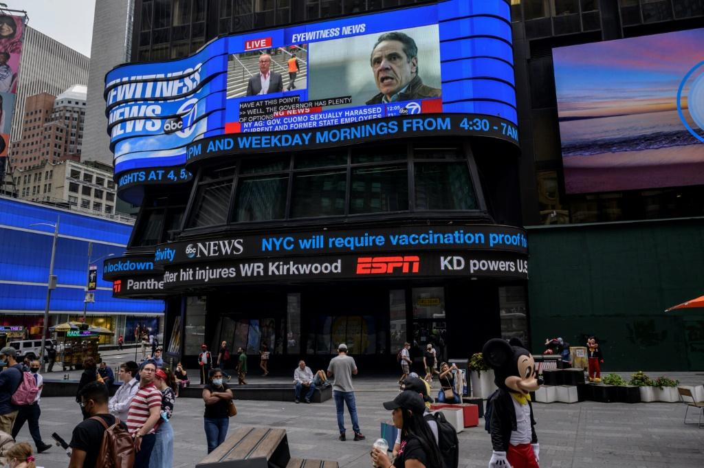 A screen shows news coverage of New York Governor Andrew Cuomo following revelations over allegations of sexual harassment, in Times Square on August 3, 2021