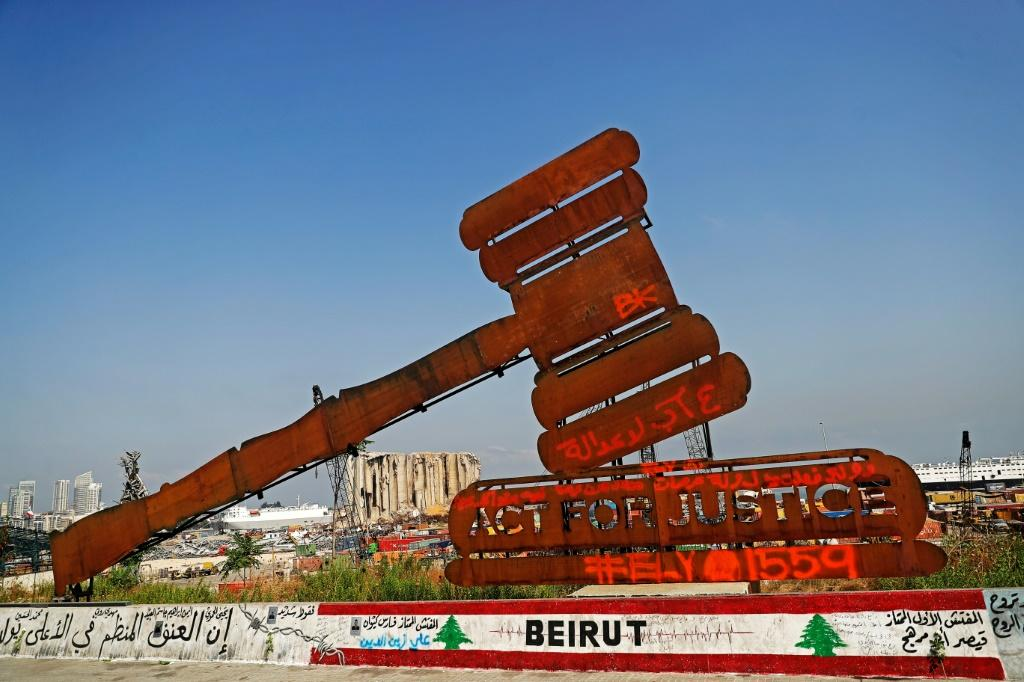 A gavel monument symbolising justice is seen in front of the damaged grain silos at Beirut port on August 4, 2021, the one year anniversary of the powerful blast