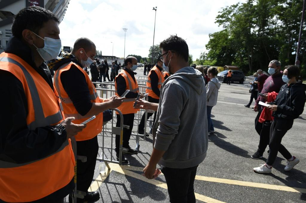 Stewards check supporters' health passes and tickets before the start of the French L1 football match between FC Metz and Lille OSC