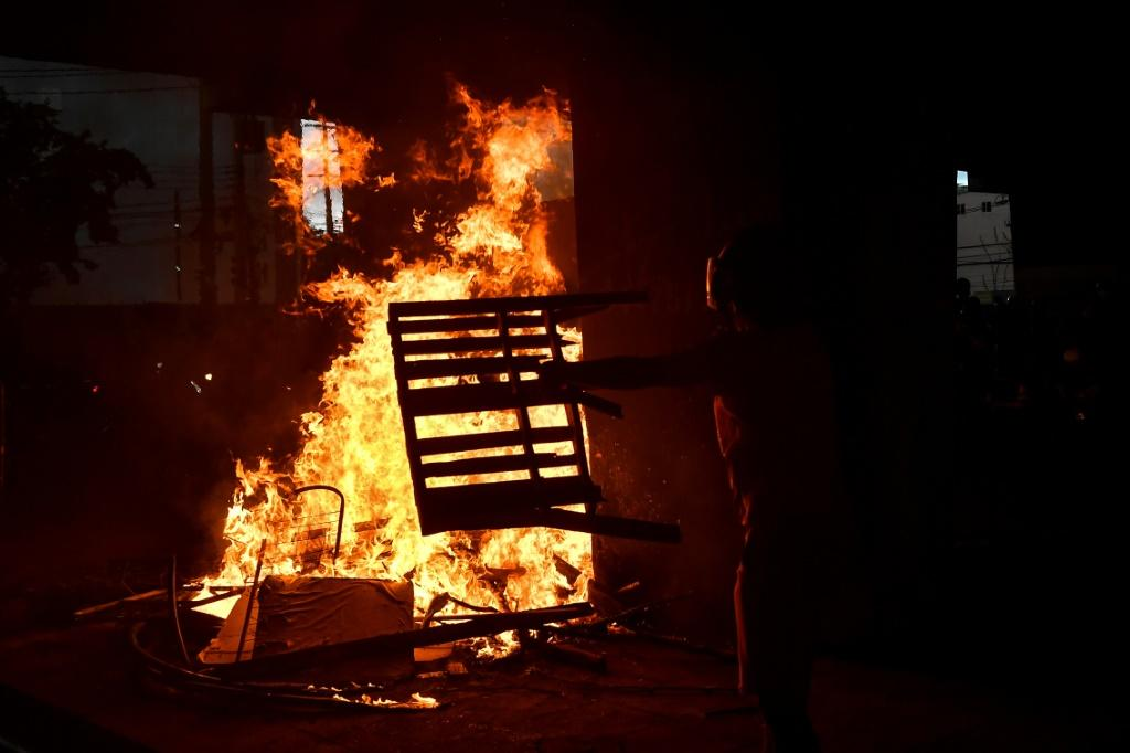 A demonstrator throws a table on a fire during the protest