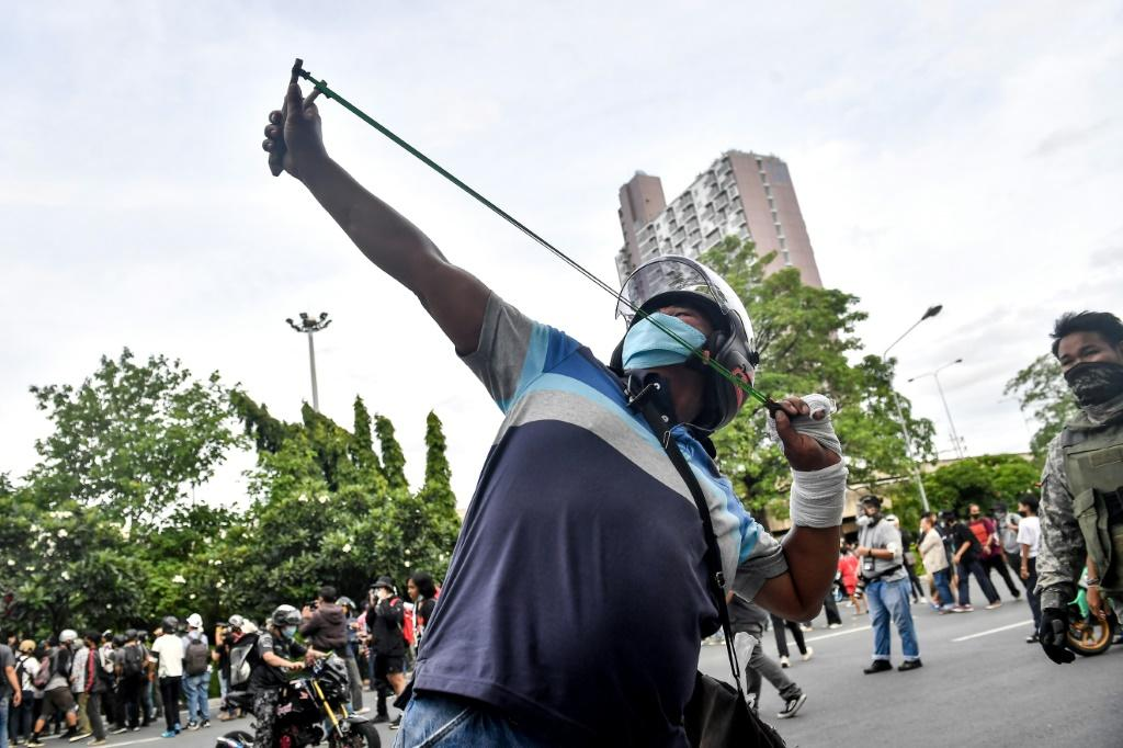 A protester uses a slingshot against police at the rally in Bangkok