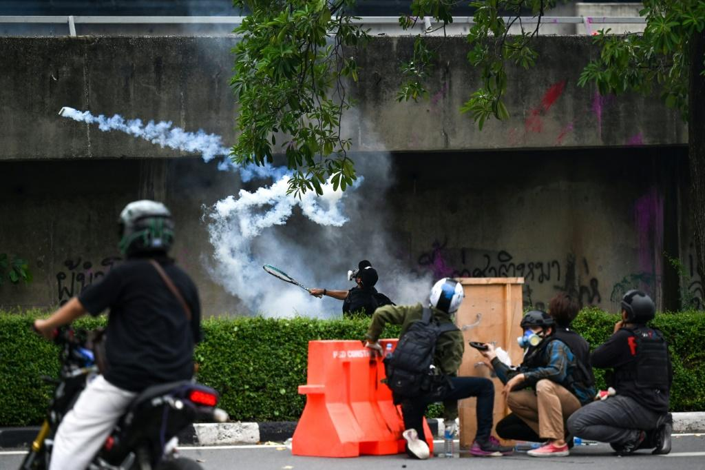 A protester uses a tennis racket to deflect a tear gas canister