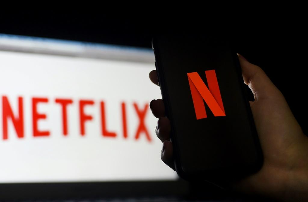 In this photo illustration a computer and a mobile phone screen display the Netflix logo in March 2020 in Arlington, Virginia